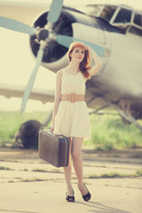 Lonely girl with suitcase at near airplane.