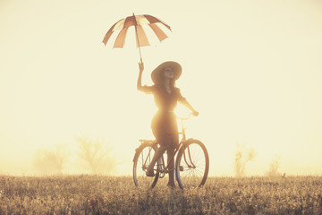 Girl with umbrella on a bike in the countryside in sunrise time