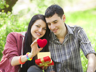 Couple with gift at green grass in the park