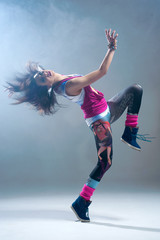 Woman in pink grunge clothes dancing in a studio.