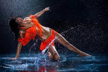 Woman dancing under rain in orange dress. Studio