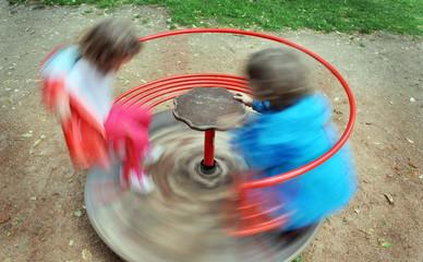 Due bambini giocano su una giostra girello