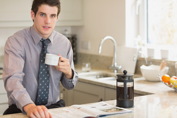 Man drinking coffee while reading newspaper