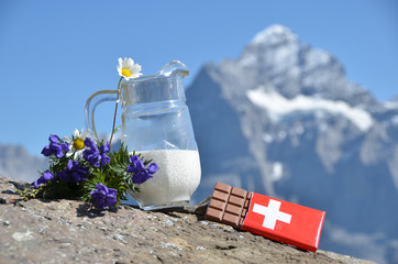 Wall Mural - Swiss chocolate and jug of milk against mountain peak. Switzerla