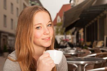 Junge Frau trinkt Kaffee / Tee und lächelt