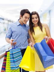 Surprised man peeking into shopping bag