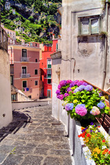 Colorful flower lined street in a coastal village in Italy