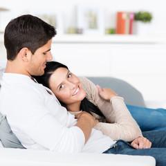 junges paar kuschelt auf dem sofa