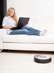 Woman lying on the sofa, and the robot vacuum cleaner cleans