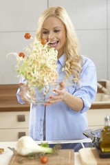 Attractive woman making salad in kitchen