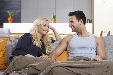 Loving couple sitting on sofa at home smiling