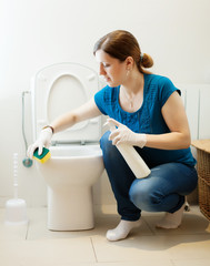 Woman cleaning toilet with sponge and cleaner