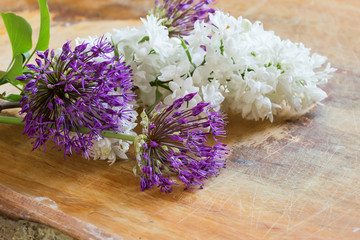 Fresh flowers of allium  and lilak on wooden table
