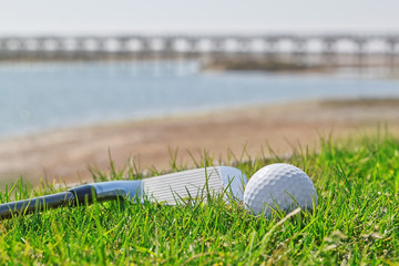Golf stick and ball on grass with a background of nature. Close-
