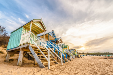 colorful beach huts at sunset