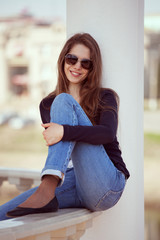 Charming woman in glasses and blue jeans