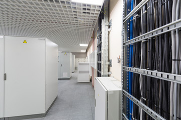 Room with rows of racks with equipment for telecom and cables.