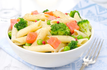 salad with pasta, salmon, broccoli, green peas in a bowl