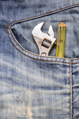 closeup of an adjustable wrench in a jean pocket