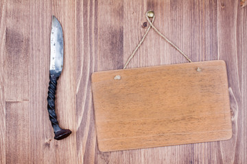 Wooden signboard with knife on planks background