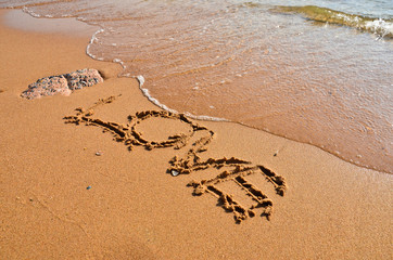 Inscription love on the wet sand of the sea