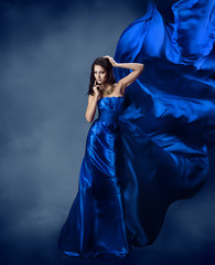Woman in blue dress  with flying silk fabric