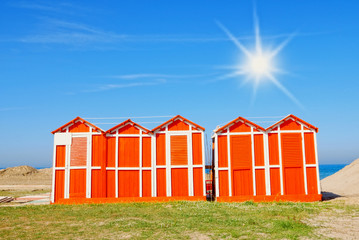 wooden cabins on the sand in rimini, italy