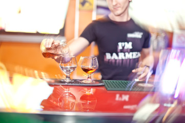 Barmen  pours brandy at the night club