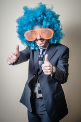 funny businessman with big orange glasses and blue wig