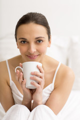 Woman in bed drinking tea