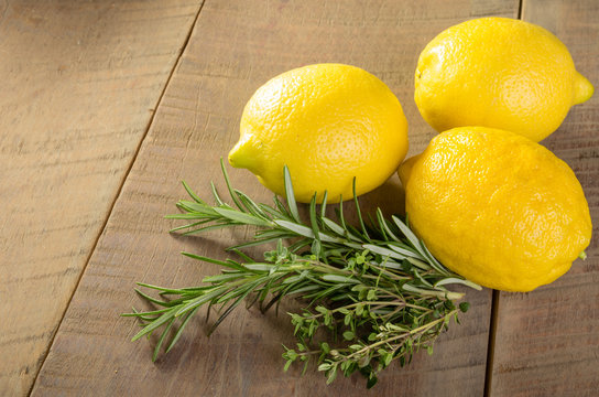 Lemons and herbs on a wooden table