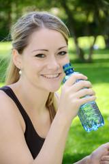Freundliche junge Frau trinkt Wasser