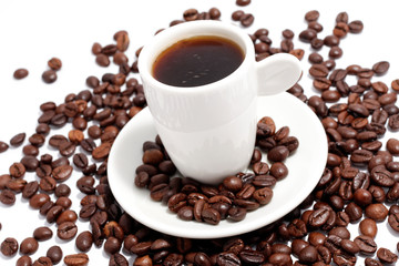 a cup of espresso with coffee beans on white
