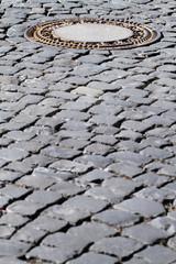 Kopfsteinpflaster mit Gullydeckel