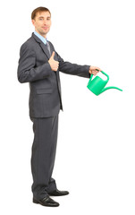 Young businessman pouring water from watering can isolated