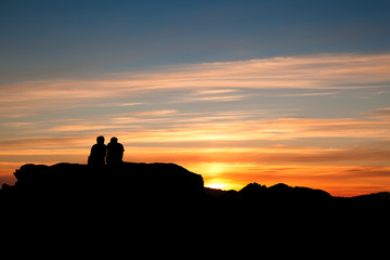 Couple having relax on top of a rock at sunset