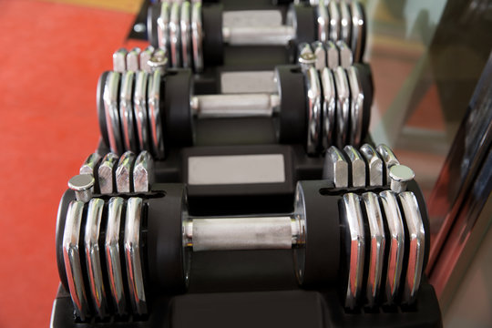 Adjustable weight dumbbells in a row with selective focus