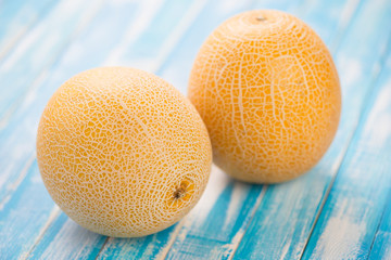 Horizontal shot of two ripe Galia melons on wooden boards