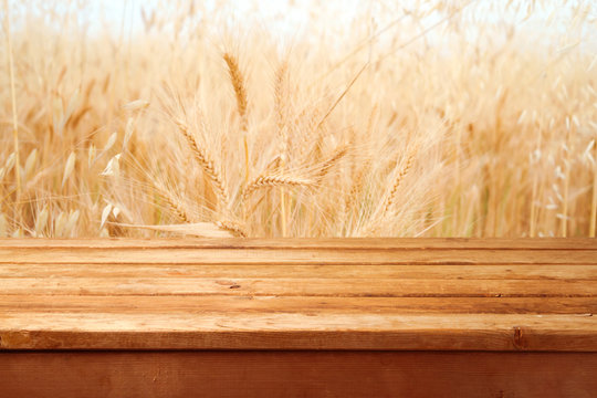 Empty wooden deck over wheat field background