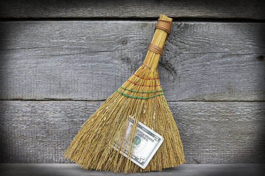 Image of broom with dollars, close-up
