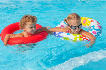 little girl and little boy playing in the pool with rubber ring