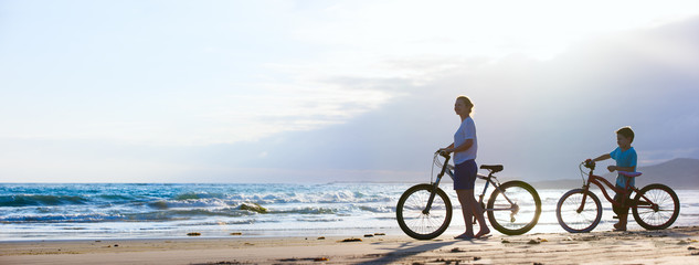 Wall Mural - Mother and son biking at beach