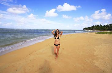 Young woman in bikini walking on Las Terrenas beach, Samana peni