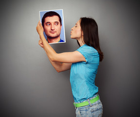 woman kissing the picture of young man