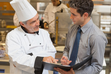 Waiter and chef discussing the menu