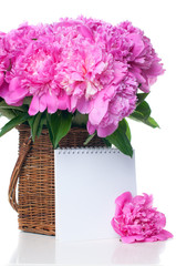 Bouquet of pink peonies in a wicker basket isolated