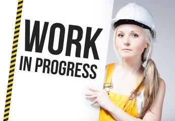 Worker holding work in progress sign on information board
