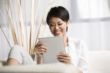 Chinese woman sitting on sofa using Digital Tablet