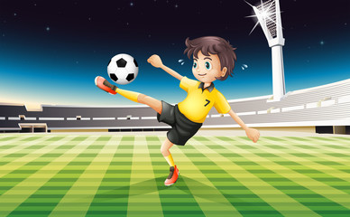 A boy in his yellow uniform playing soccer at the field