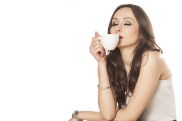 satisfied girl enjoying the smell of her coffee